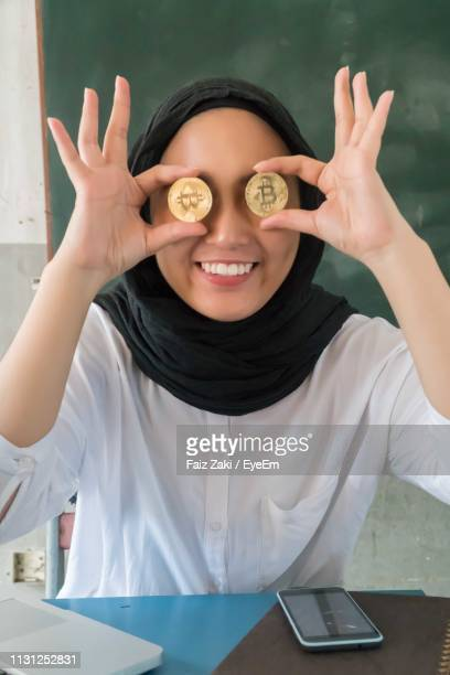 woman in hijab covering eyes with bitcoins at home - kryptowährung stock-fotos und bilder