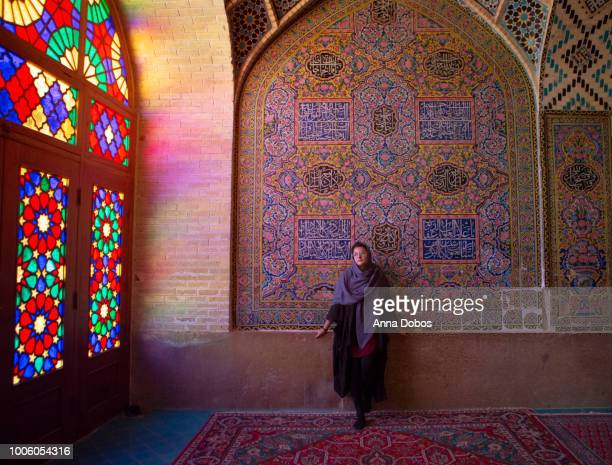 woman in hijab standing against tiled wall in mosque - iranian culture stock pictures, royalty-free photos & images