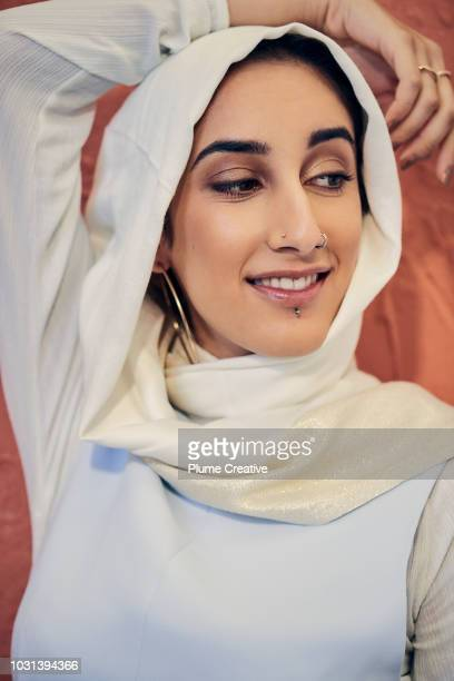 Woman in hijab with arm raised over head