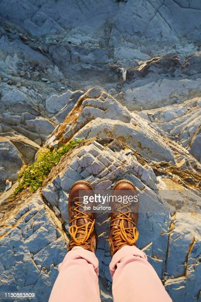 woman in hiking boots standing on a rock - high up stock pictures, royalty-free photos & images