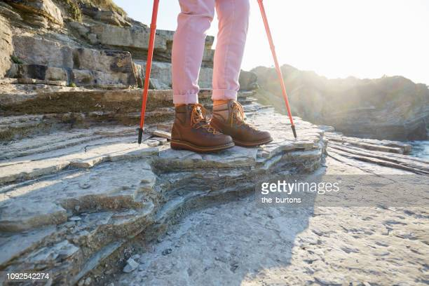 Woman in hiking boots standing with nordic walking poles on a rock