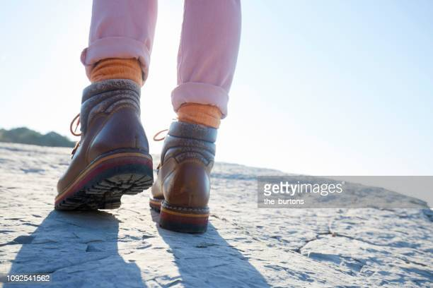 woman in hiking boots walking on a rock by the sea - ピレネーアトランティーク ストックフォトと画像