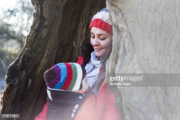 Woman in hollow tree, carrying young baby in sling