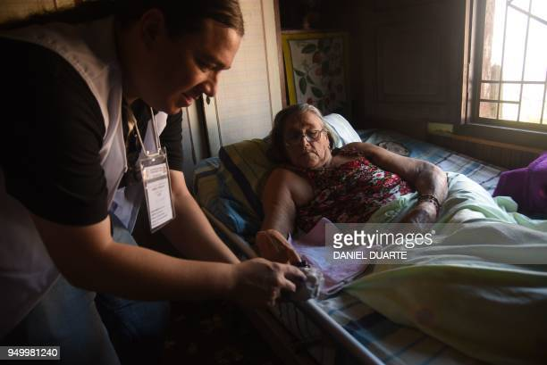 A woman in home medical rest is assisted to vote during presidential elections in Asuncion on April 22 2018 Opinion polls give Mario Abdo Benitez of...