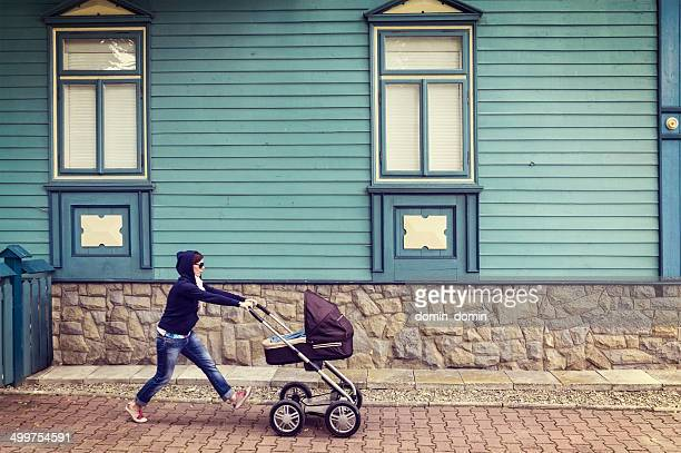 Woman in hoodie with baby stroller on walk, old house