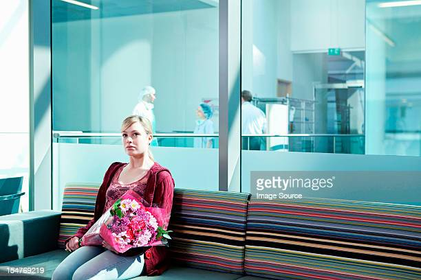 Woman in hospital waiting room with bouquet