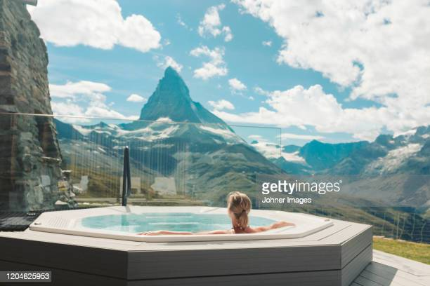 woman in hot tub looking at mountains - wellbeing stock-fotos und bilder