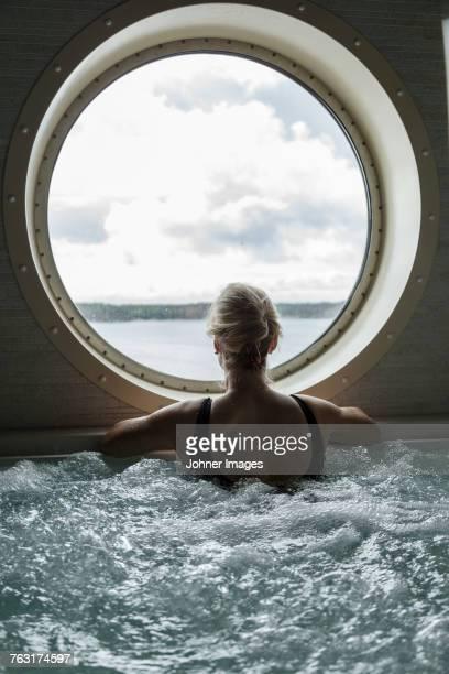 Woman in hot tub looking through window