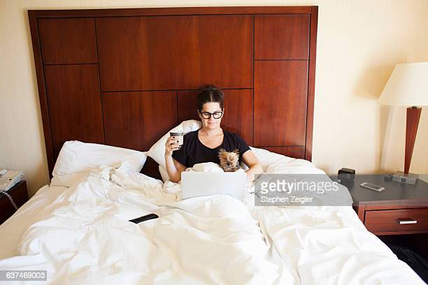 woman in hotel bed on working on her laptop