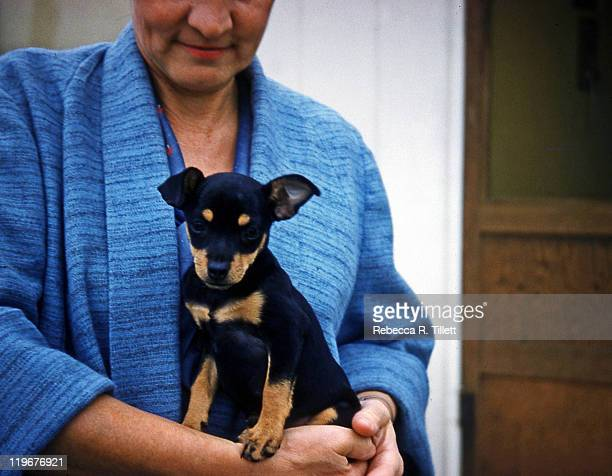 Woman in housecoat holding small dog