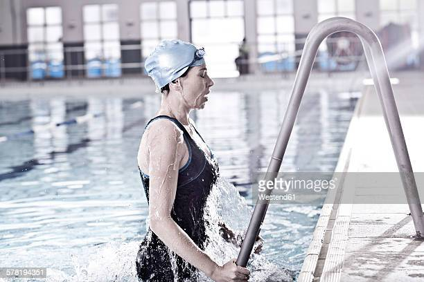 Woman in indoor pool at pool edge