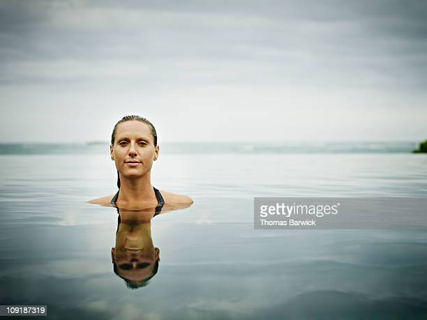 Woman in infinity pool at tropical resort