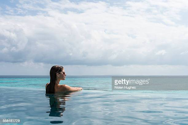 Woman in infinity pool looking off into distance