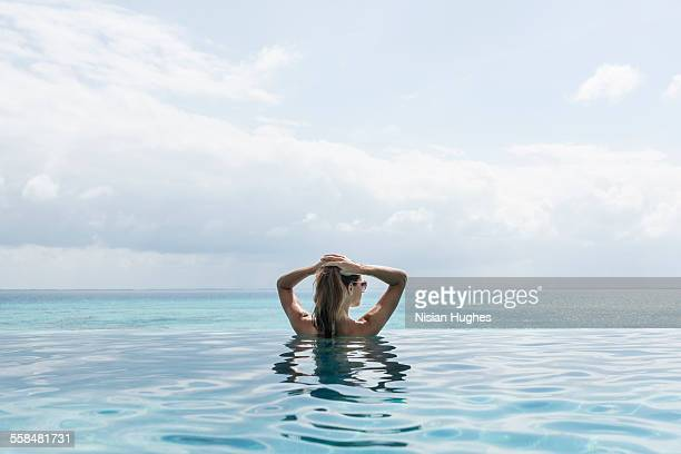 Woman in infinity pool looking out into distance