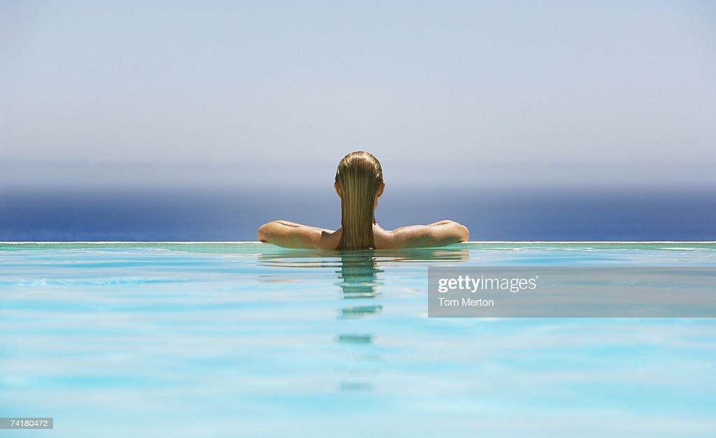 Woman in infinity pool : Stock Photo