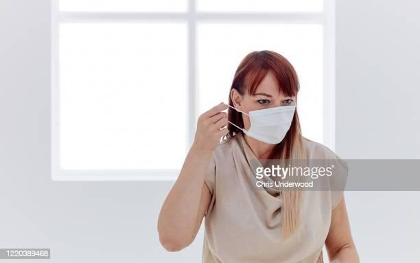 woman in isolation wearing a surgical mask, with a big bright window behind - munskydd ensam bildbanksfoton och bilder