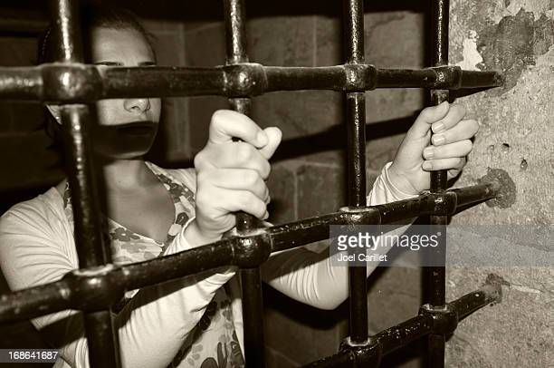 Woman in jail holding onto metal bars