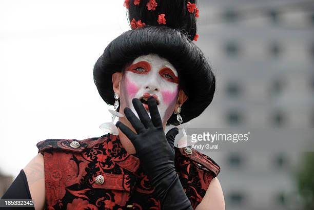 Woman in Japanese mikado style make-up and large wig covers her mouth with a black gloved hand. She is wearing a red and black brocade tunic. The...