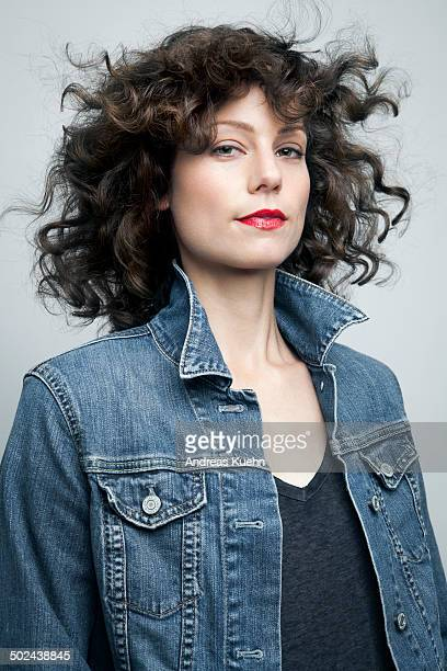 Woman in jeans jacket and red lipstick.