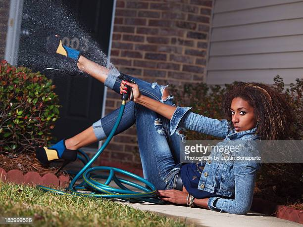 woman in jeans spraying water from a hose - charlotte long stock pictures, royalty-free photos & images