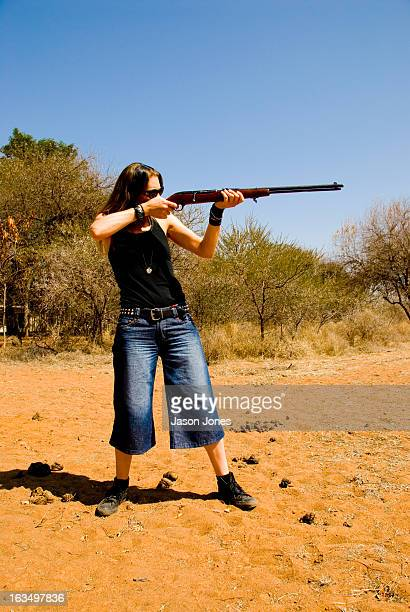 Woman in jeans takes aim with a rifle in Thabazimbi, South Africa