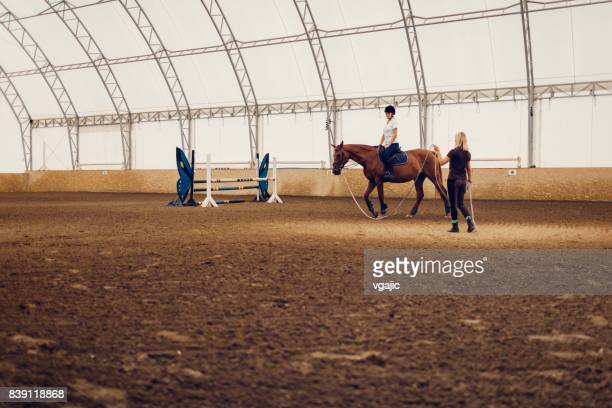 Woman in jockey's riding park with her horse