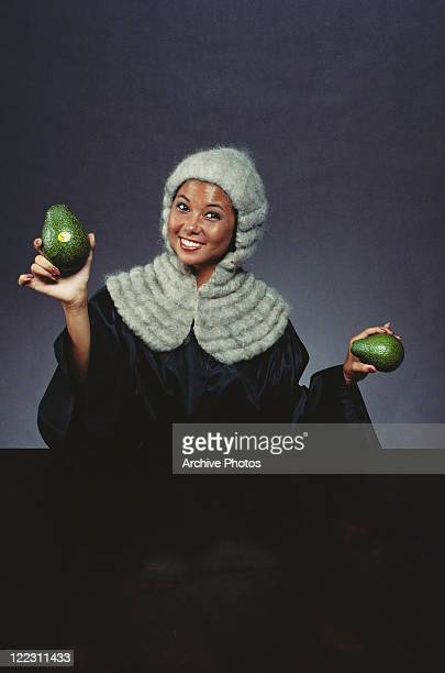 Woman in judge's robe holding avocadoes, portrait, smiling