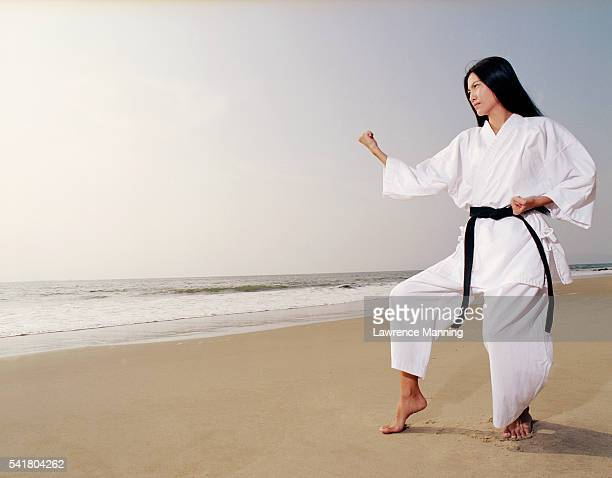 Woman in Karate Position on Beach