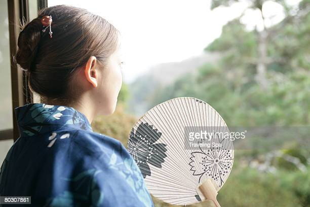 Woman in kimono and fan, staring into the garden