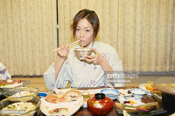 Woman in kimono eating noodles