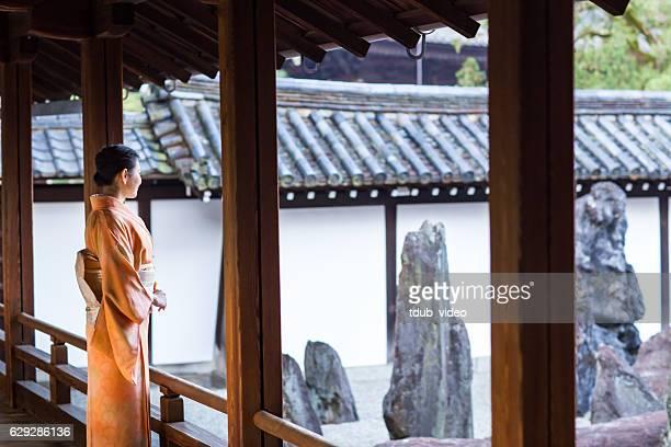 Woman in Kimono enjoying scenery at Japanese temple