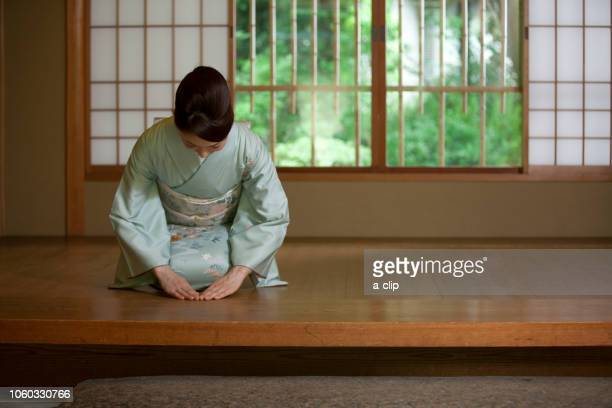 a woman in kimono greeting at the door - kimono stock pictures, royalty-free photos & images