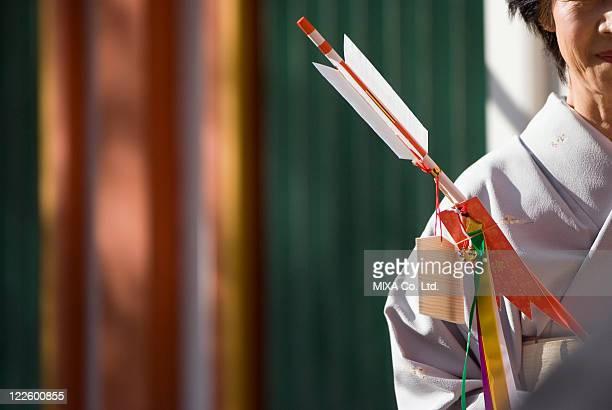 Woman in kimono holding decorative arrow