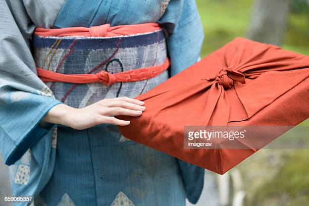 Woman in kimono holding parcel