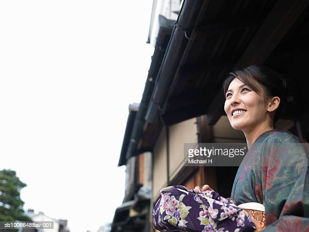 Woman in kimono holding wrapped gift, outdoors