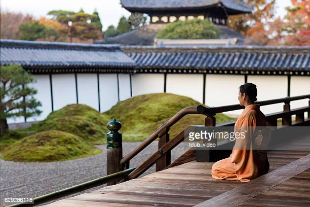 Woman in kimono kneeling at a Japanese temple