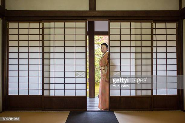 Woman in kimono looking through sliding doors in a temple