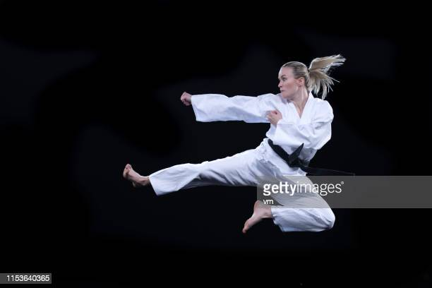 woman in kimono performing a flying kick against a black background - taekwondo stock photos and pictures