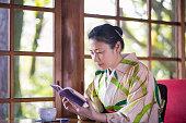 woman kimono reading book cafe