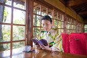 woman kimono reading book cozy restaurant