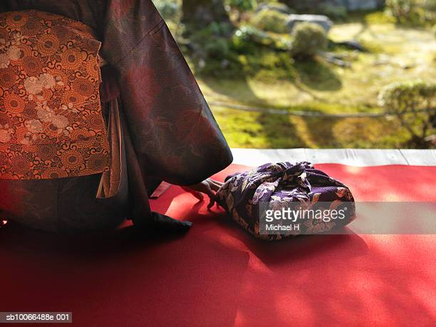 Woman in kimono sitting beside wrapped gift, outdoors