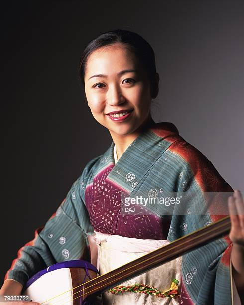 a woman in kimono smiling and playing shamisen, front view - shamisen stock photos and pictures