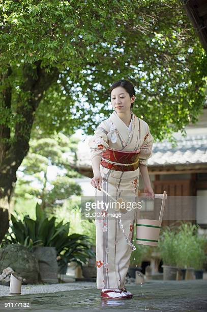 woman in kimono sprinkling water with dipper - bamboo dipper stock photos and pictures