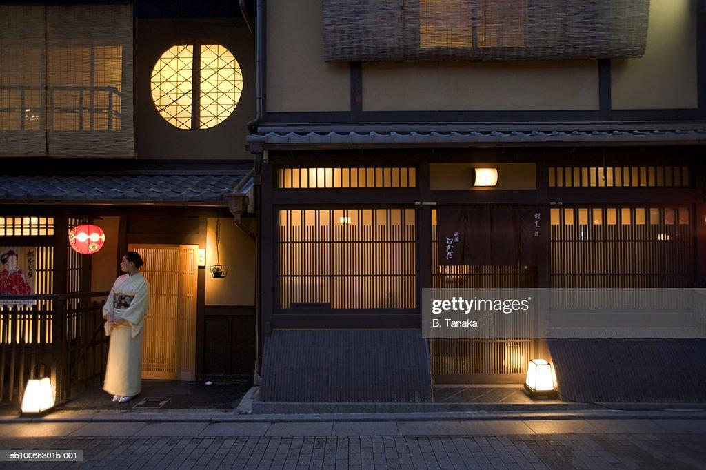 Woman in kimono standing outside restaurant : Foto stock