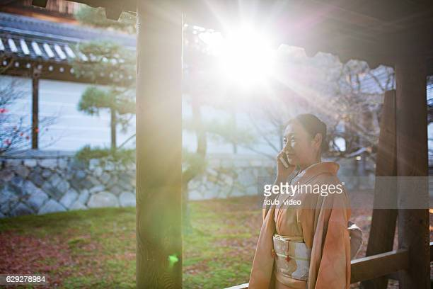 woman in kimono talking on smartphone in a japanese temple - obi sash stock pictures, royalty-free photos & images