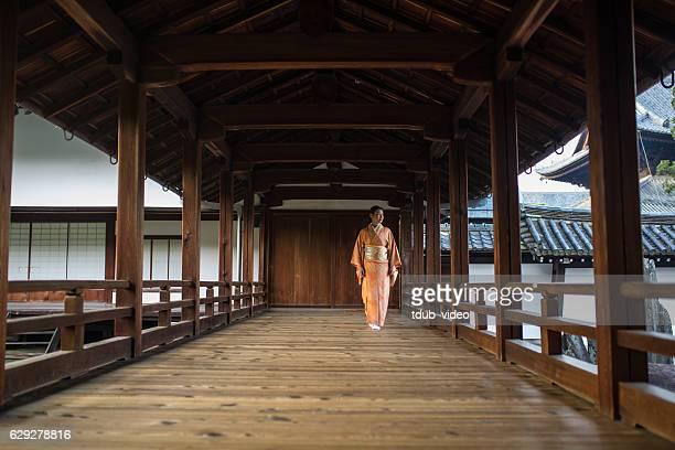 Woman in kimono walking through a Japanese temple