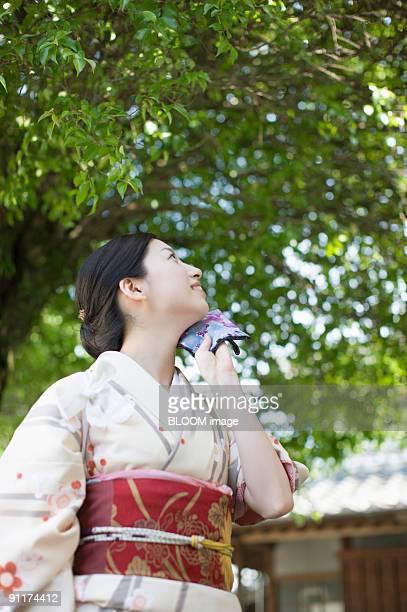 Woman in kimono wiping sweat with handkerchief