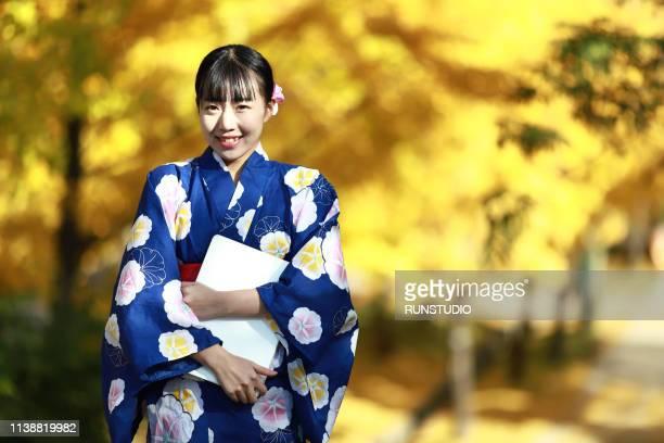Woman in kimono with laptop in autumn park