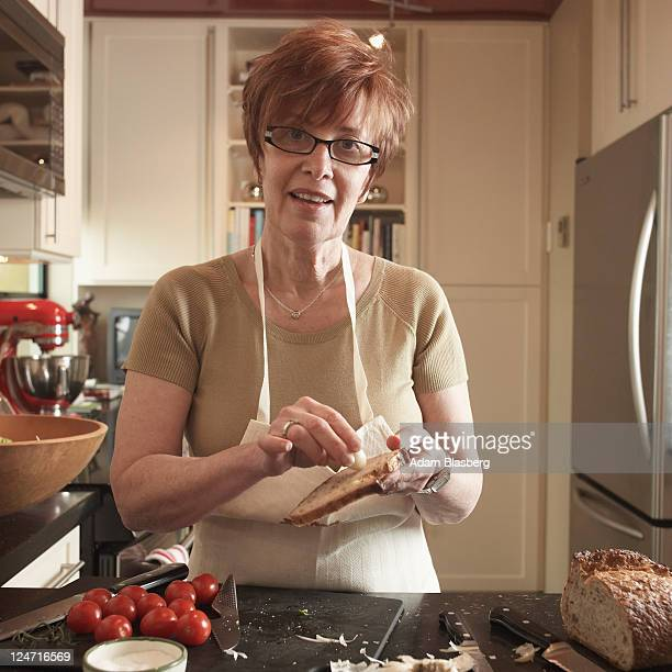 Woman in kitchen cooking, demonstrating garlic on toast