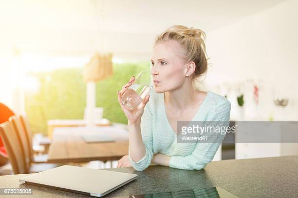 Woman in kitchen drinking glass of water